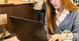 Studentessa asiatica che lavora ad un computer portatile ad una caffetteria Fotografia Stock
