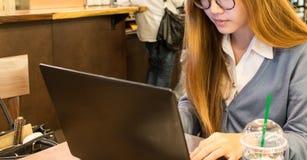 Studentessa asiatica che lavora ad un computer portatile ad una caffetteria Fotografie Stock Libere da Diritti