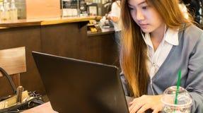 Studentessa asiatica che lavora ad un computer portatile ad una caffetteria Fotografie Stock