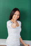 Studentessa asiatica che mostra i pollici su immagine stock libera da diritti