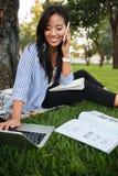 Studentessa asiatica felice che si siede sull'erba con il computer portatile e la conversazione Fotografia Stock