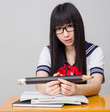 Studentessa asiatica in uniforme scolastico che studia con una matita di grande misura Immagini Stock