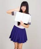 Studentessa asiatica in uniforme scolastico con il libro aperto Fotografia Stock Libera da Diritti