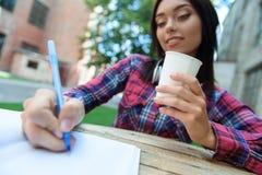 Studentessa astuta che fa le note in taccuino Fotografie Stock