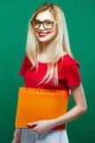 Studentessa astuta sorridente in occhiali con il fascicolo di documenti in mani che stanno sul fondo verde in studio Fotografia Stock