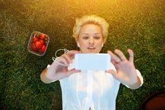 Studentessa attraente che prende immagine con la macchina fotografica del telefono delle cellule mentre trovandosi su un prato in Immagine Stock Libera da Diritti