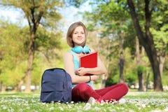 Studentessa bella con il libro e le cuffie che si siedono su un g Fotografia Stock Libera da Diritti