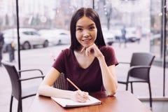 Studentessa castana che lavora al compito Immagine Stock