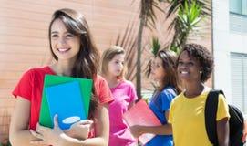 Studentessa caucasica in camicia rossa con altri studenti internazionali Fotografia Stock