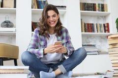 Studentessa che controlla media sociali prima dell'ottenere indietro allo studio, sedentesi sul pavimento contro l'interno domest immagini stock