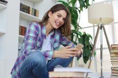 Studentessa che controlla media sociali prima dell'ottenere indietro allo studio, sedentesi sul pavimento contro l'interno domest immagini stock libere da diritti