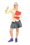 Studentessa che dà un pollice su e che tiene i taccuini Immagine Stock