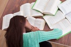 Studentessa che dorme con i libri allo scrittorio dell'aula Immagini Stock