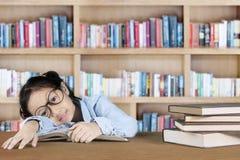 Studentessa che dorme nella biblioteca Fotografie Stock