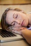Studentessa che dorme nella classe sul suo computer portatile Immagini Stock