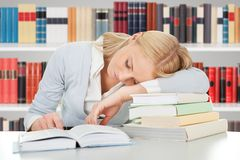 Studentessa che dorme in una biblioteca Immagine Stock