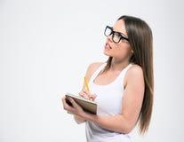 Studentessa che fa le note in blocco note e nel distogliere lo sguardo Immagini Stock Libere da Diritti