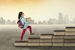 Studentessa che fa un passo sulla scala dei libri Immagine Stock Libera da Diritti