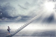 Studentessa che fa un passo sulla scala verso la luce solare Fotografie Stock