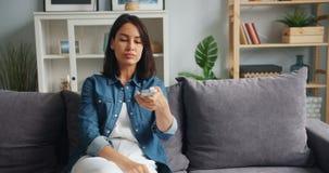 Studentessa che guarda TV in appartamento facendo uso del sorridere telecomandato divertendosi video d archivio