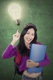 Studentessa che indica ad una lampadina luminosa Immagine Stock Libera da Diritti