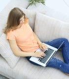 Studentessa che lavora con il computer portatile che mette sullo strato Fotografia Stock Libera da Diritti
