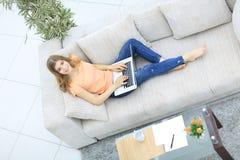 Studentessa che lavora con il computer portatile che si siede sul sofà e che esamina macchina fotografica Fotografia Stock