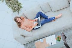 Studentessa che lavora con il computer portatile che si siede sul sofà e che esamina macchina fotografica Immagine Stock