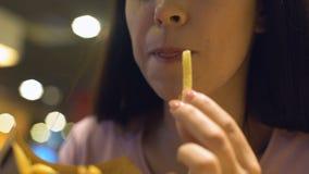 Studentessa che mastica il primo piano delle patate fritte, generazione degli alimenti a rapida preparazione, obesità stock footage