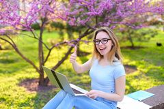 Studentessa che mostra i pollici su e che prepara per l'esame con il computer portatile e le carte nel parco Immagine Stock
