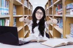 Studentessa che mostra i pollici su nella biblioteca Fotografia Stock