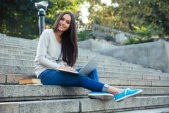 Studentessa che per mezzo del computer portatile all'aperto Fotografia Stock