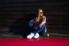 Studentessa che per mezzo del telefono delle cellule mentre riposando sulla città universitaria dopo le conferenze Fotografie Stock Libere da Diritti