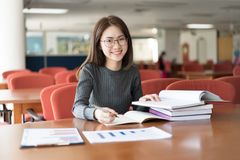 Studentessa che prende le note da un libro alla biblioteca, giovane donna asiatica che si siede alla tavola che fa le assegnazion fotografia stock libera da diritti