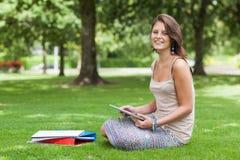 Studentessa che si siede con i libri al parco Fotografie Stock Libere da Diritti