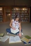 Studentessa che si siede con i libri sul pavimento delle biblioteche Immagine Stock