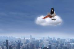Studentessa che si siede con il computer portatile su una nuvola Fotografia Stock