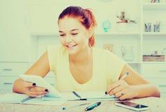 Studentessa che si siede e che studia all'interno Immagini Stock Libere da Diritti