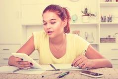 Studentessa che si siede e che studia all'interno Fotografie Stock Libere da Diritti