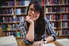 Studentessa che si siede nella biblioteca Immagini Stock Libere da Diritti
