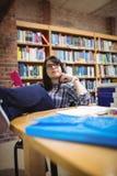 Studentessa che si siede nella biblioteca con il telefono cellulare Immagine Stock
