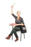 Studentessa che si siede su una presidenza e che solleva la sua mano Fotografia Stock Libera da Diritti