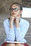 Studentessa che si siede sui punti Immagini Stock