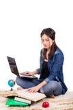 Studentessa che si siede sul tappeto con i libri ed il computer portatile Fotografia Stock