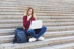 Studentessa che si siede sulle scale e che lavora con il computer portatile all'aperto Fotografie Stock Libere da Diritti