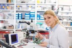 Studentessa che studia apparecchio elettronico con un microprocessore Fotografie Stock Libere da Diritti