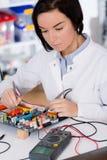 Studentessa che studia apparecchio elettronico con un microprocessore Immagini Stock