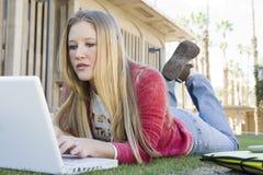 Studentessa che studia con il computer portatile Immagine Stock