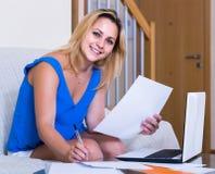 Studentessa che studia con il computer portatile e le note all'interno Fotografia Stock