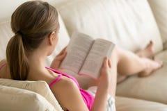 Studentessa che studia con il manuale a casa Fotografie Stock